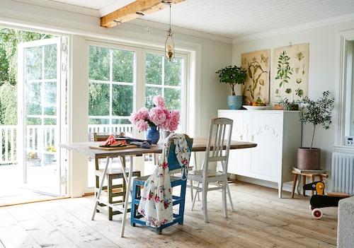 Från Jons och Claras egenhändigt byggda matbord i köket kan man njuta av den härliga utsikten. Den fina lilla lampan, skolplanscherna och linneskåpet är några av Claras loppisfynd. Järvsöstolarna - det vill säga den gröna och den blå, har många år på nacken och följde med i husköpet.