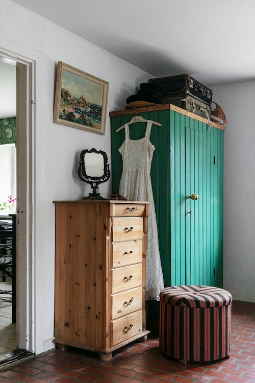 I hallen utanför köket står ett rejält gammalt skåp i original. Samma gröna kulör visade sig vara den ursprungliga färgen på väggpanelen i skolsalen som var brunmålad när Stella och Ludvig flyttade in. På skåpet hänger Stellas farmors brudklänning.