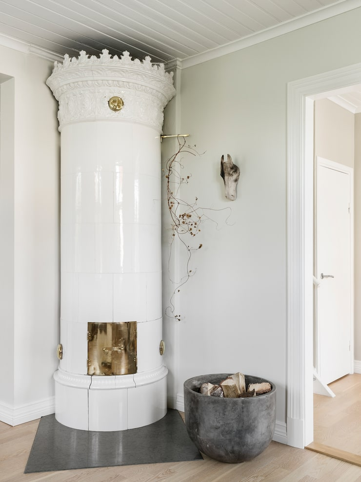 Kakelugnen är inte bara en värmekälla – det ger också rummet karaktär. Hästhuvudet har Anna Gärberg gjort.