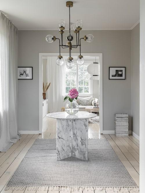 Vy in i köket genom ett genomgångsrum. Vintagebord i marmor, Art N Deco. Vas Pallo, från Skruf, Newport.