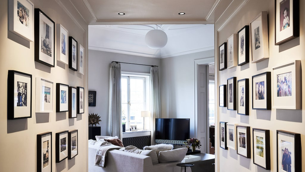 Två väggar fyllda med svartvita fotografier.
