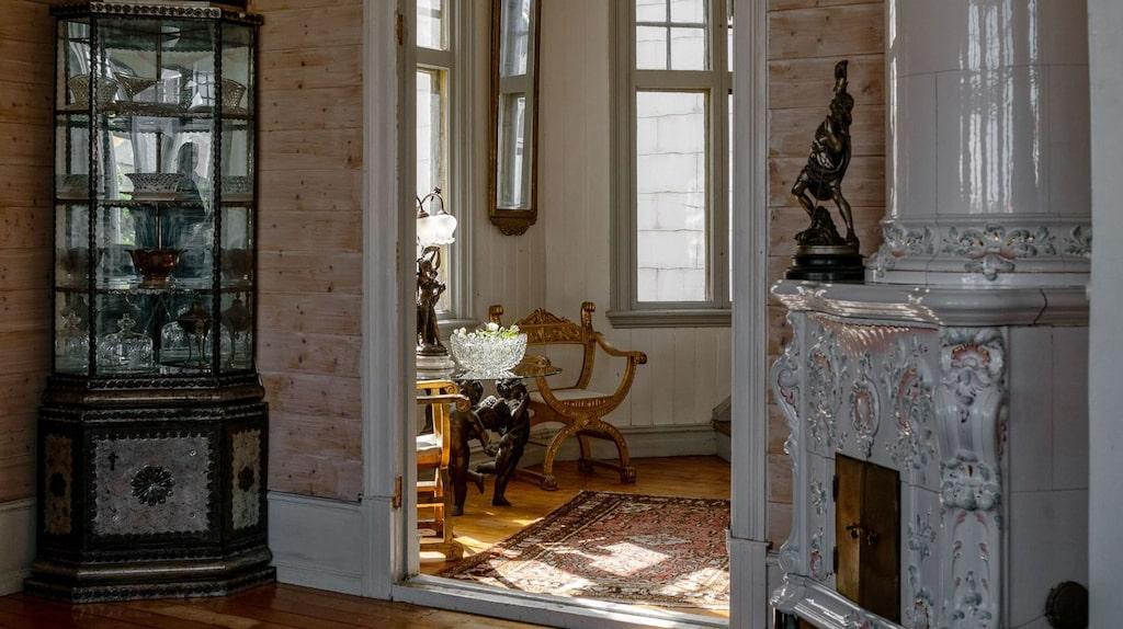 Det är en unik chans att ta över detta hus med så många möjligheter och häftig historia. Här en av villans många kakelugnar och ett antikt skåp.