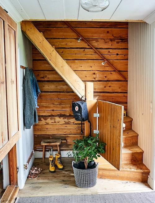 I hallen sätter timret och den gamla trappan stämningen. Skåp på väggen, loppisfynd. Korg, Korbo.