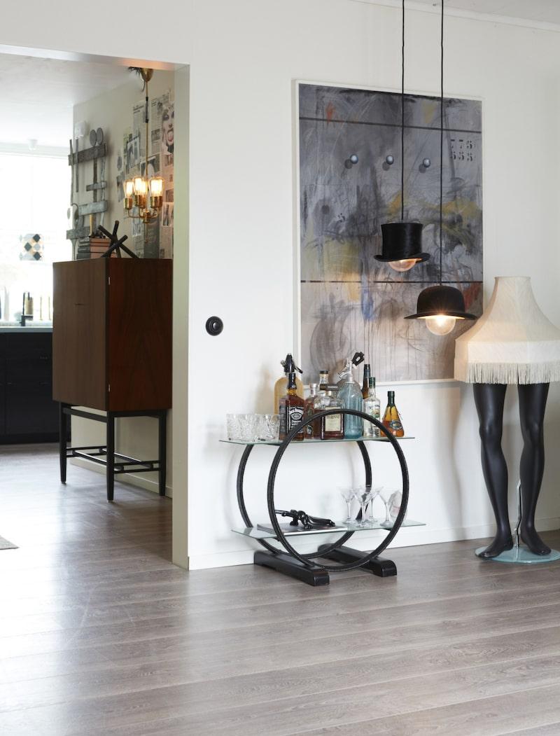 Hattlampor. På väggen hänger en målning som Sandie vann i ett konstlotteri på sitt förra jobb. Hattlamporna och lampan på skyltdockebenen har Sandie gjort själv. Barvagnen i art deco-stil är köpt på Blocket.