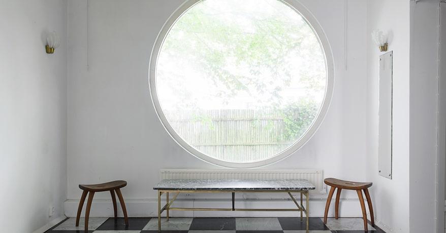 Redan i entréhallen förstår man vem som har ritat huset, vi möts av ett stort runt fönster och ett svartvitt golv.