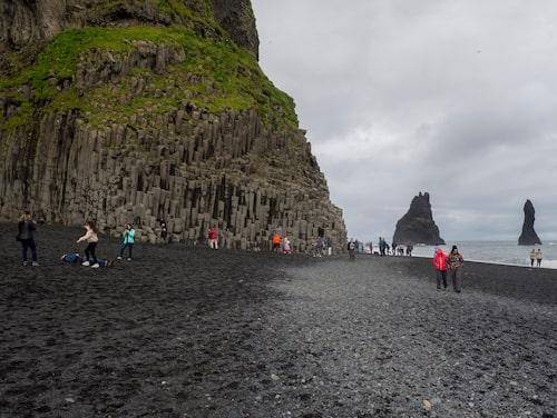 Besökare promenerar längs stranden i Vík í Mýrdal den 4 juli.