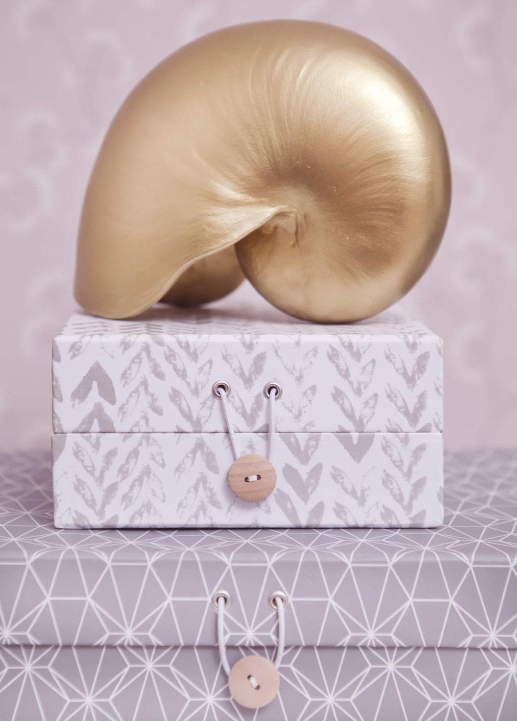 Förvaring. Boxar av papper, 79-129 kronor, Hemtex. Snäcka av keramik, 450 kronor, Atélje Alt.