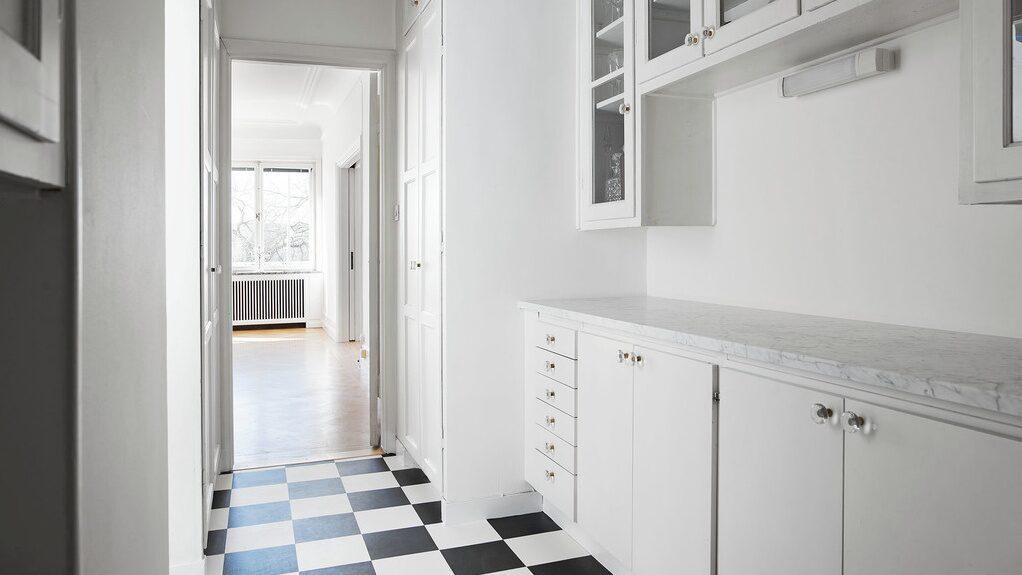 Serveringsgången som binder samman matsalen och köket. Här finns vitrinskåp i original för porslin samt linneskåp. Nyrenoverat och med marmorbänkskivor ovan underskåpen och golv i schackrutigt.