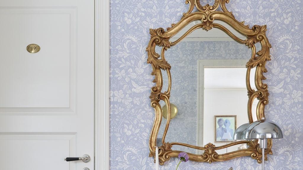 Den snirkliga rokokospegeln och ett träbord med patina har kombinerats med en modern lampa i krom.