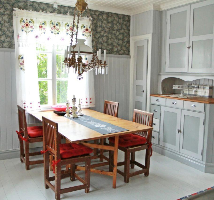 Lantligt kök i grå toner<br>Kristallkronan och möblerna i Bagarstugans kök är arvegods. Tapeten är gammal, tapetrullarna hittade Karin gömda på vinden.
