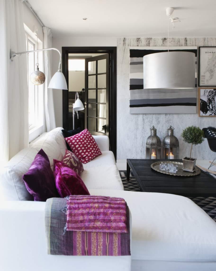 Det svartvita bryts ibland av med starka färger. Vita lampor från Bestlite. Taklampan har Camilla målat om i silver, liksom vardagsrumsbordet som målats svart. Kuddar från Svenskt tenn och Indien.
