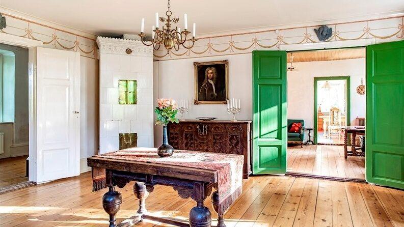 Nedervåningen har genomgående trägolv och de tre större rummen som finns här har alla en kakelugn.