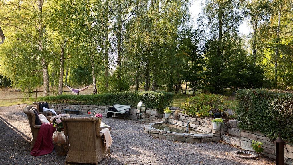 På husets baksida finns en gruslagd uteplats med en damm och en mur av öländsk kalksten.