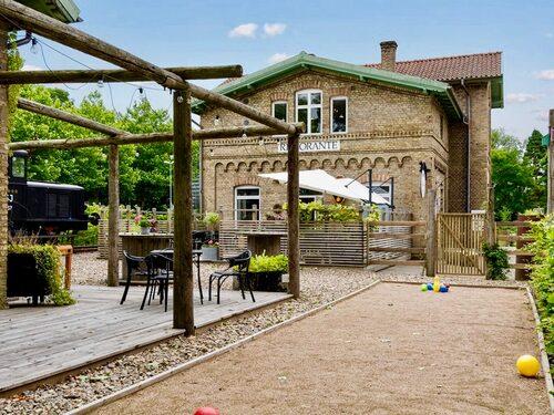 Tomten är stor och rymmer både boulebana, trädäck till ena annexet samt till stationshuset/restaurangen.