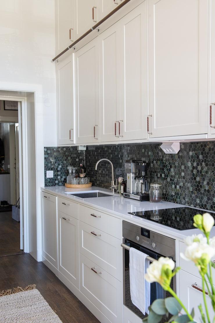 """Köket i tidstypisk stil kommer från Järfälla Kök, beslag från Beslag Design. Bänkskivan är av komposit """"Noble supreme white"""" från Technistone."""