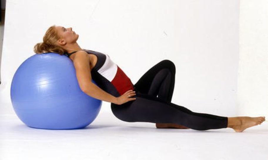 7-A. Benpress: Sätt dig på huk på golvet med bollen som ryggstöd. Håll händerna i sidorna och sträck ut ett ben rakt fram.