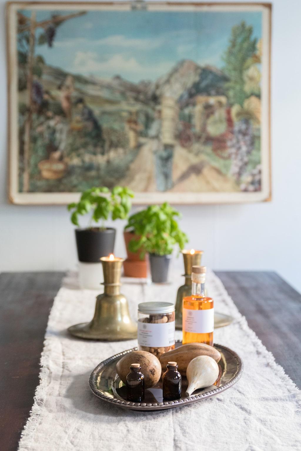 Skrynklig linnelöpare med fransade kanter från Axlings Linne och ett fat från Pottery Jo passar på det mörka bordet. De stora ljusstakarna i mässing kommer ursprungligen från en kyrka.