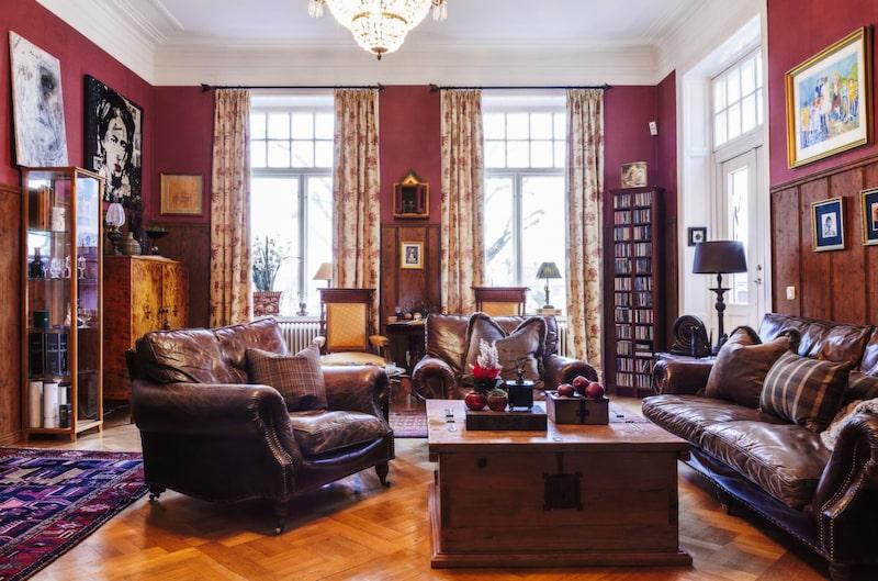 Ombonat. En varm, röd ton omger rummet och skinnmöblerna från Artwood. Bordet kommer från Möbelhuset NO1 i Borås. Oljemålningar från Charles Roka. Kuddar från Artwood och Gant.