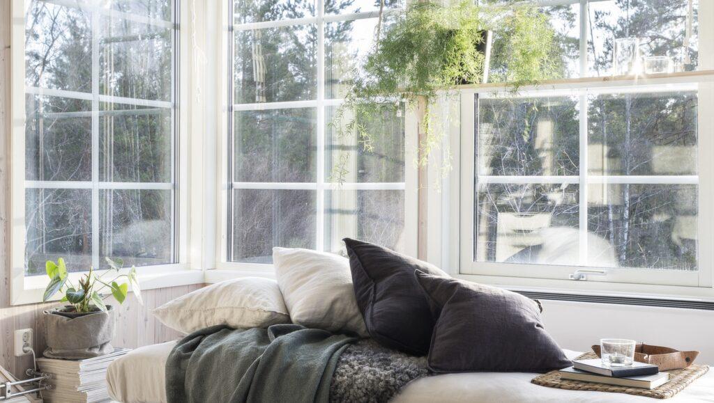 Sällskapsrummet har sex fönster i tre väderstreck så även om det inte är sommar så har man härligt ljusinsläpp. Divanen är från Ikea, ullplädarna från Mio. Kuddar i linne från H&M home.
