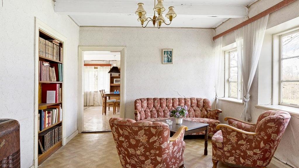 Vardagsrummet har inbyggd bokhylla och parkettgolv...