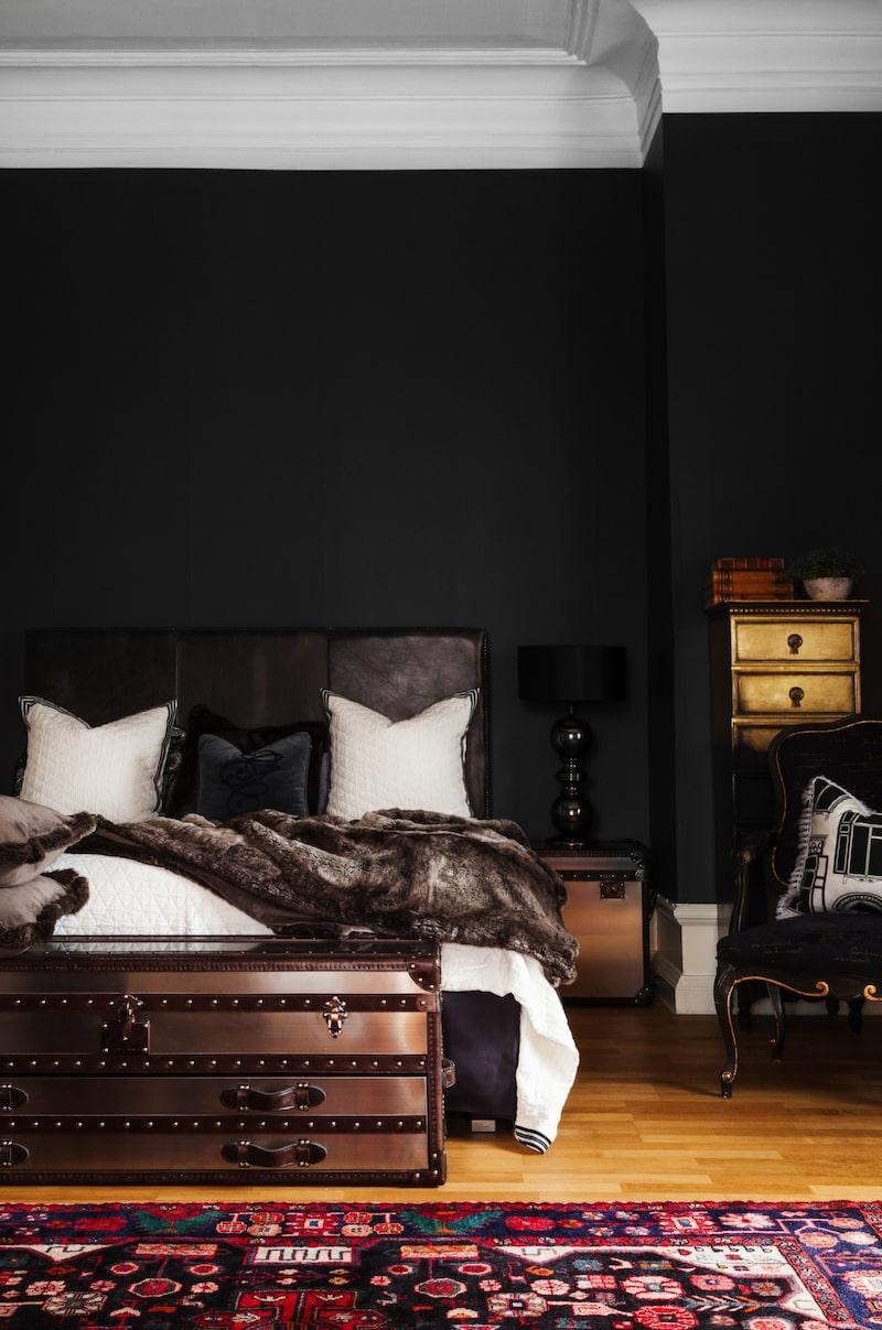 Maskulint. Sovrummet går i samma stil som resten av huset och är maskulint inrett med möbler från Artwood. Byrån i guld kommer från Mercedes Murat. Karmstolen är köpt i en butik på Strandvägen i Stockholm och kudden är från Design by E. Sängkläder från Gant.