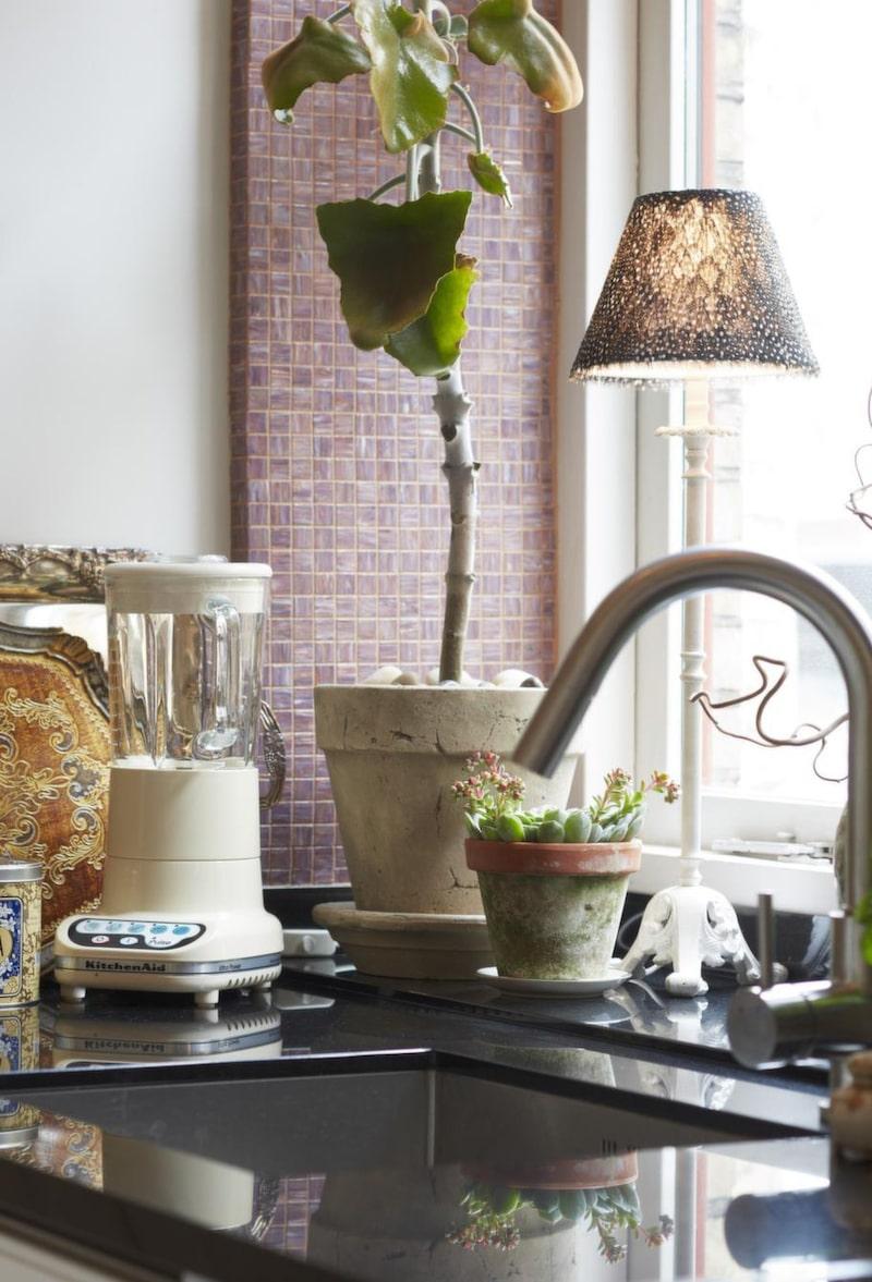 Köket är inrett med moderna detaljer, rustika krukor och växter.