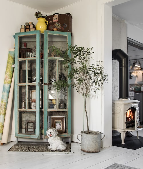Skåpet har Åsa och Andreas byggt av gamla franska fönster och fyllt med favoritsaker från resor, antikaffärer och loppmarknader. Porslinshund, Bodil Vintage. Vitemaljerad kamin, Jötul.
