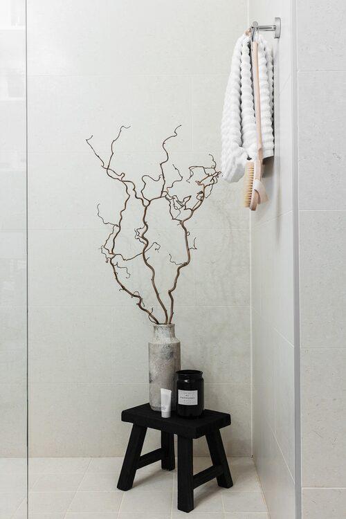 I hemmets badrum finns en stor dusch med plats för dekoration i ena hörnan. De svarta detaljerna blir en fin kontrast mot det ljusa kaklet. Pall och vas, Zara Home.
