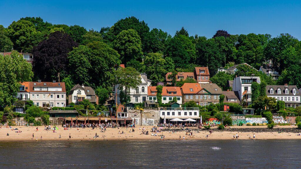 Elbes norra flodstrand kantas av tjusiga villor, grönska och sandstränder.