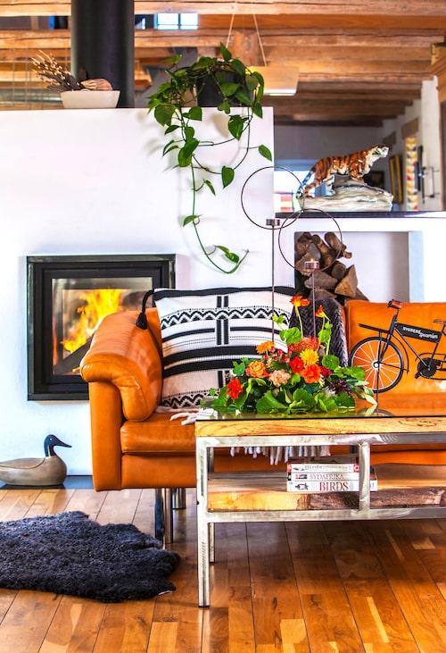 Skinnsoffan är en av två som ropats in på auktion. Soffbordet har Peter byggt med gamla alplankor och en glasskiva. Tigern på den avgränsande spishyllan är från Peters mormor och piggsvinstaggar och snäckor är resefynd. De runda ljusstakarna är från I AM interior.
