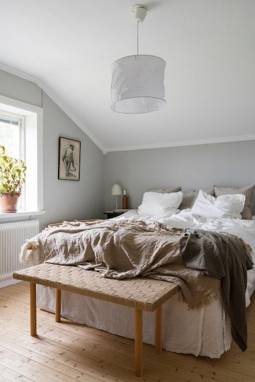 Väggarna i sovrummet är målade i kulören Lapptussans dusk från Nordsjö, en ljust gråbeige färg som gör rummet harmoniskt och vilsamt. Sängkläderna kommer från Ikea, sängkappan från Himla, överkastet från Lager 157, taklampan från Mio. Bänken har Ida och Fredrik gjort själva.