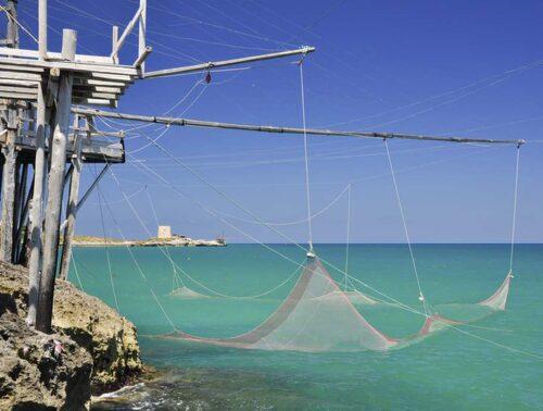 På Garagno-halvön fiskar fiskarna fortfarande med traditionella nät från bryggorna.