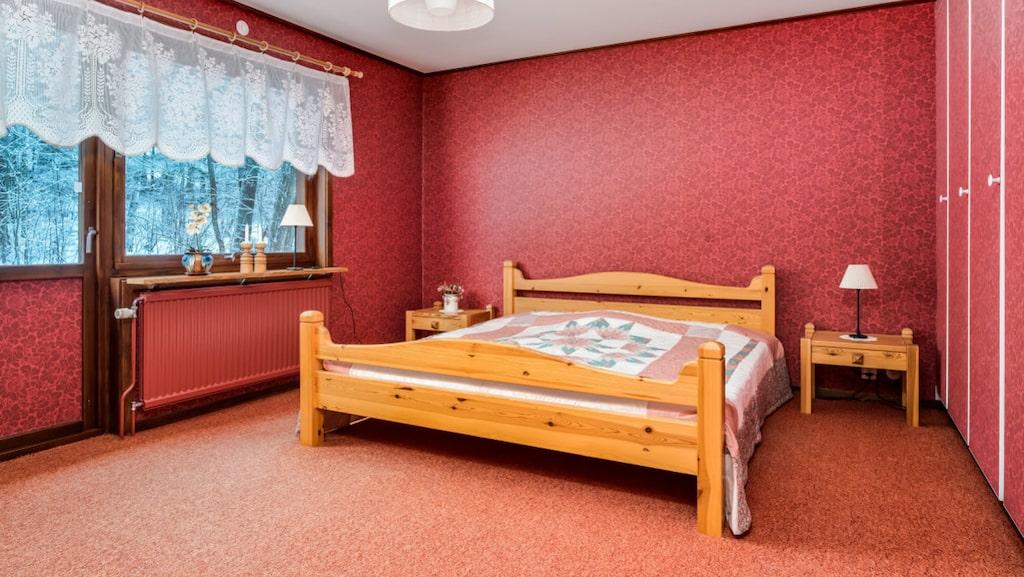 Sovrum med röd textilmatta och röda tapeter.
