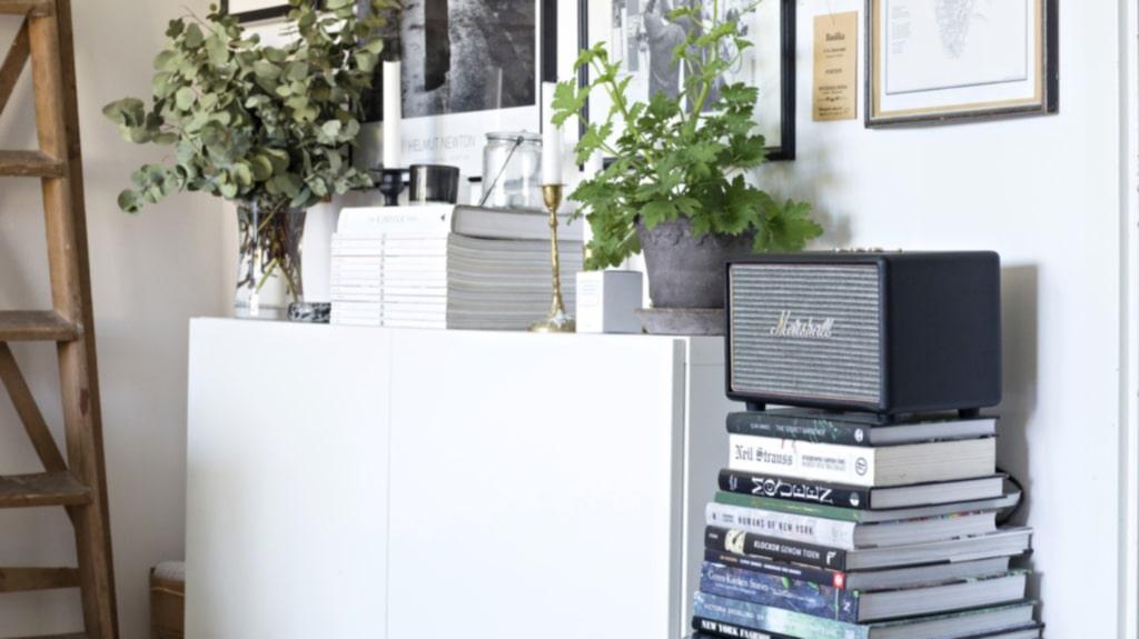 Tavelvägg. Förvaringsskåpet från Ikea rymmer mycket. Tavlorna är en mix av köpta tavlor, presenter från släktingar och foton på familjen. På skåpet ryms också en bunt torkad eucalyptus.