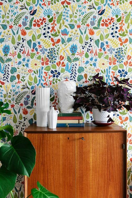 Tapet Herbarium, design Stig Lindberg, Boråstapeter. Teakskåpet är fyndat på loppis och de vita keramikvaserna är från Upsala Ekeby. I Steningekrukan står en yvig triangeloxalis, även kallad lyckoklöver.