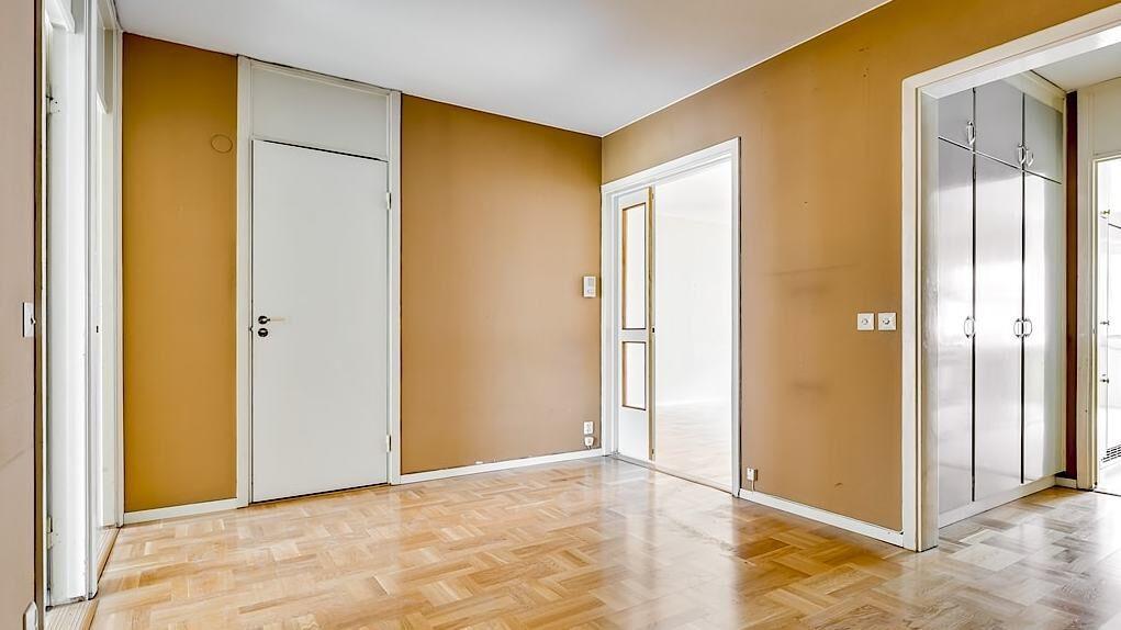 Stor mellanhall med massor av inbyggda garderober. Hallen har parkettgolv och strukturtapeter i uppiggande aprikos färg.
