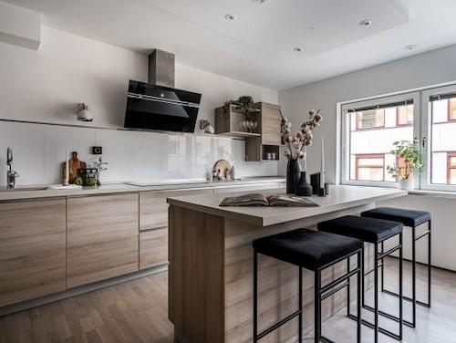 Köket har luckor i trä och integrerade handtag.
