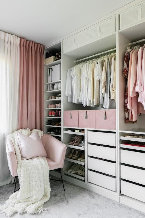 En öppen garderobslösning täcker en hel vägg i sovrummet. Eftersom Sabina tycker om att hålla ordning blir de färgkoordinerade raderna av kläder, skor, prydliga lådor och fack som en effektfull del av inredningen. Garderober från Ikea. Fåtölj Ellos. Pläd, Ikea. Kudde, H&M Home.
