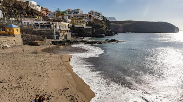 Standen Sardina del Norte ramas in av färgglada hus och en klippvägg.
