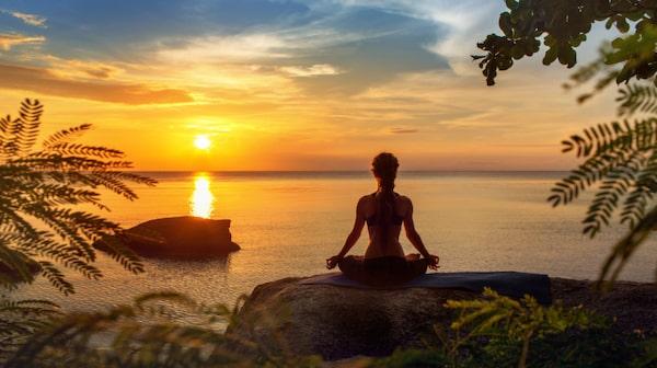 Hitta lugnet med hjälp av yoga i solnedgången.