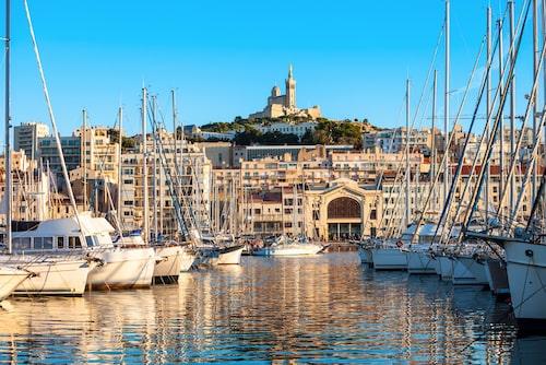 Från den gamla hamnen ser man bort mot Marseilles högsta punkt där kyrkan Notre Dame de la Garde ruvar.