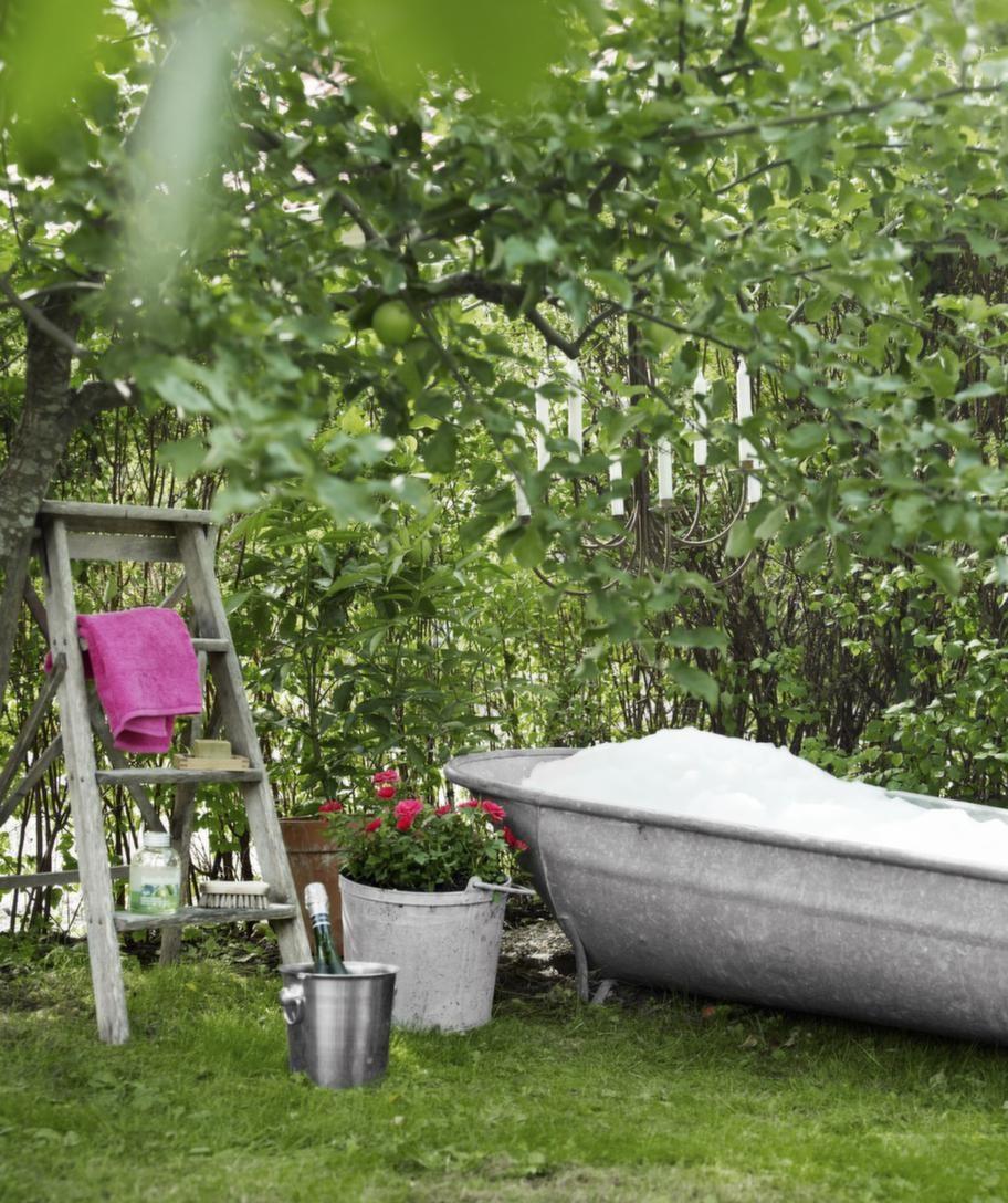 <strong>Bada ute.</strong> Badhörnan är en liten pärla bland trädgårdens överraskningar. Här kan man ta ett skumbad under äppelgrenarna i solnedgången och skapa extra stämning genom att tända stearinljusen i den rostiga ljuskronan ovanför. Ishinken med skumpa står redo, och allt annat man kan tänkas behöva finns på den gamla trästegen. Zinkbadkaret har hon hittat i en antikaffär på Österlen.