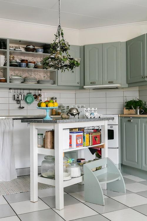 Mitt i familjens kök står en praktisk avställningsbänk med en tillhörande liten trappstege i samma nyans som köksluckorna. Klinkergolvet har Mia själv målat schackrutigt med golvfärg i två olika nyanser.