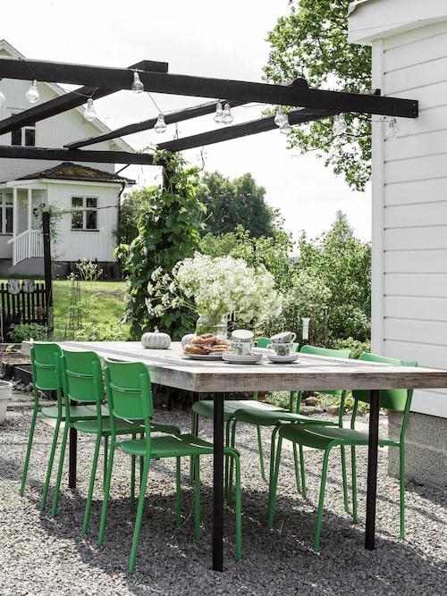 Pergolans rustika matbord är ett hemmabygge av gamla brädor. Ljusslingan drivs av solceller och tänds i skymningen. Stolar, Ikea.
