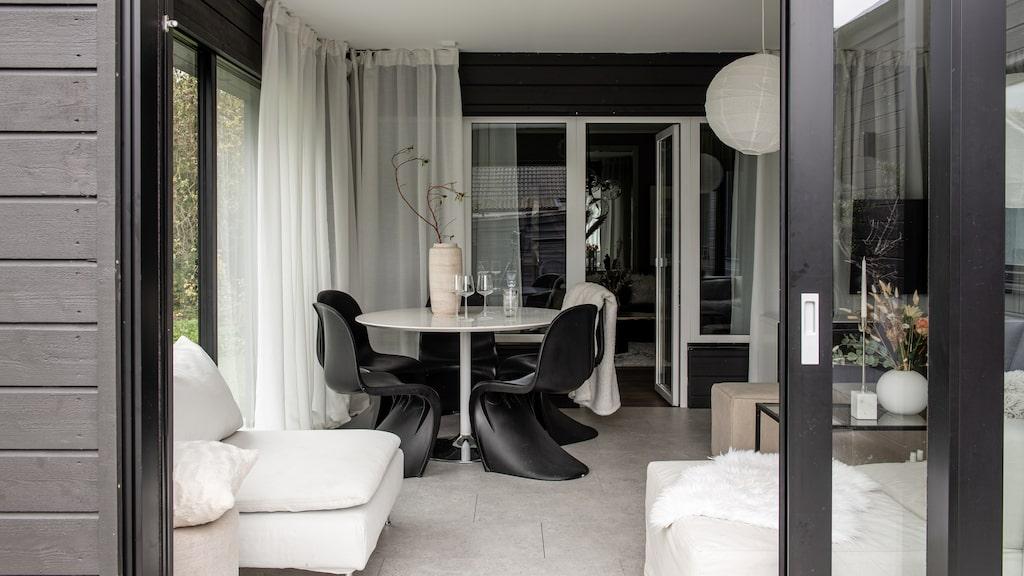 Uterummet är möblerat i svart och vitt. Soffa, lampor och bord, Ikea. Matplatsstolarna och det runda bordet är köpt second hand. Gardiner, Ikea. Sittpuffar Mio. Vas på soffbordet, från Cooee.