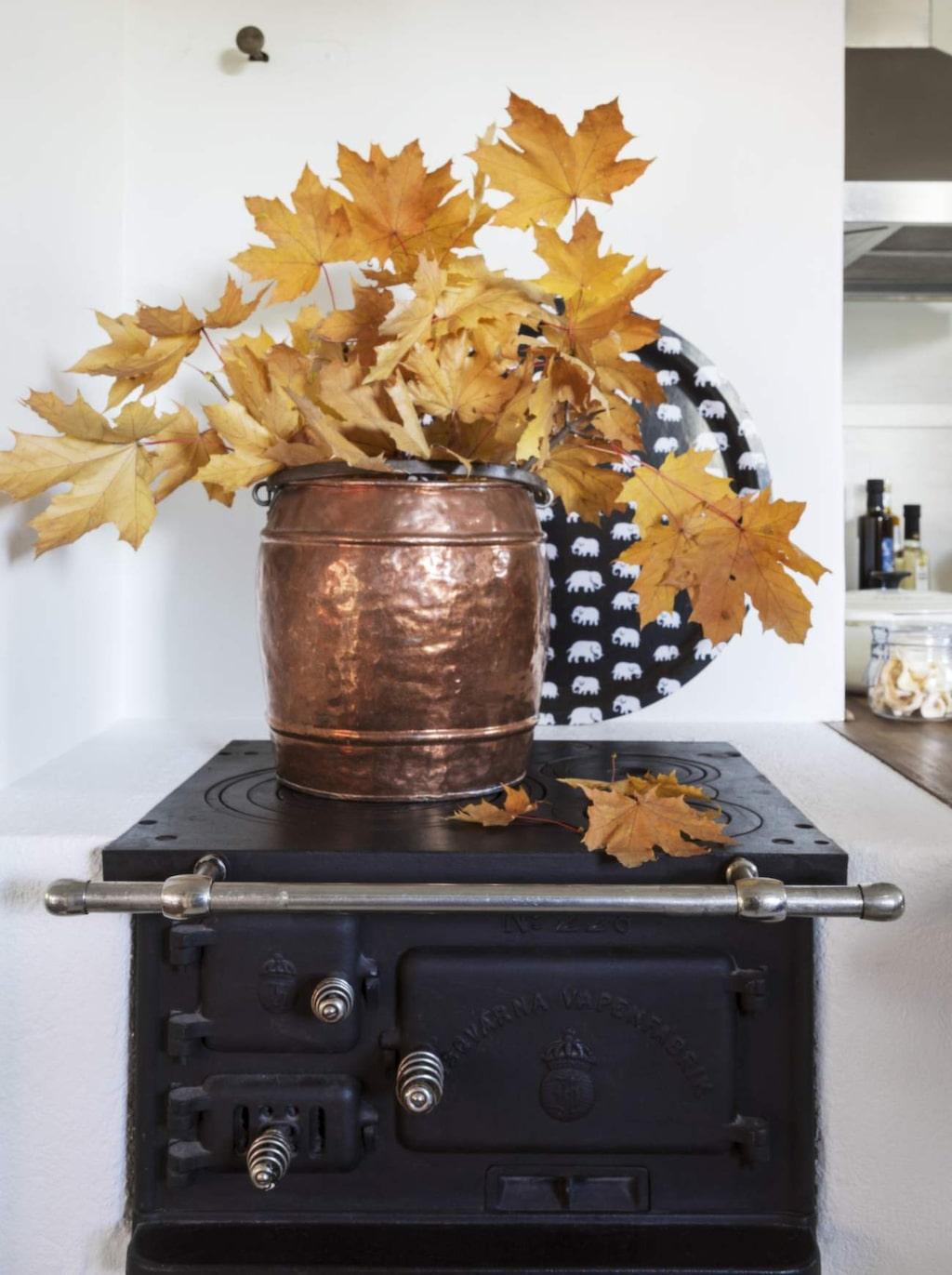 Vedspisen är original och stod tidigare i köket på ovanvåningen, men fick flytta ner när köket renoverades. Kopparhink från Jens föräldrahem, Bricka från Svenskt tenn.