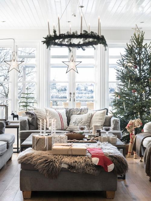 Hela storfamiljen samlas i vardagsrummet på julafton. De små barnen brukar ivrigt springa runt och kika efter tomten i alla fönster. De randiga kuddarna är sydda av gamla mjölsäckar. Bord, Artwood. Adventsstjärnor, PR Home.