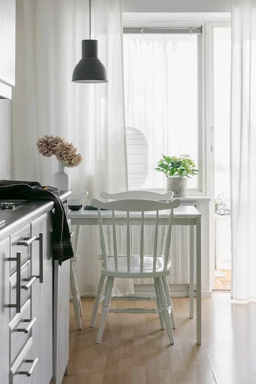 I köket fungerar matplatsen huvudsakligen som skriv- och arbetsbord. Äter gör man vid matplatsen i vardagsrummet. Pinnstolarna är arvegods. Taklampa, Ikea. De skira vita gardinerna samlar upp och sprider ljuset från den inglasade balkongen.