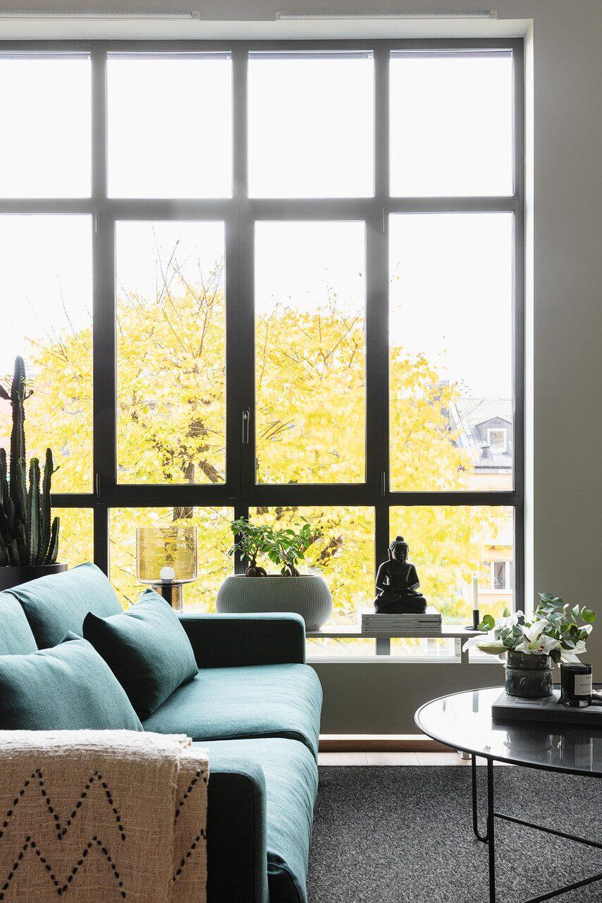Utanför vardagsrummets stora fönster står flera träd som skyddar mot insyn från grannhuset mittemot. Oval kruka, Plantagen. Fönsterlampa, House Doctor. Pläd, Rolf & Friends.