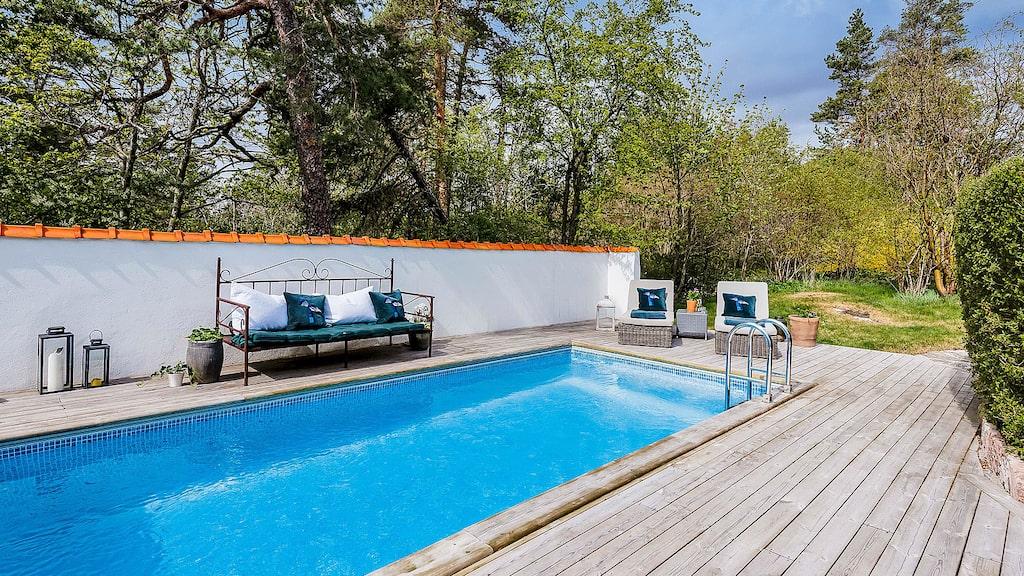 Vacker insynsskyddad och lekvänlig trädgård med flera träd och buskar samt pool med soldäck.
